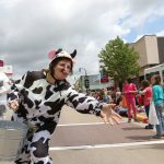 Frances Skora, dressed as a cow, throws candy to children during the Dairyfest Parade in downtown Marshfield June 4, 2016.
