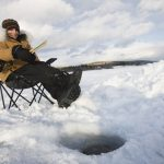 Woman sits at Canadian ice hole fishing --- Image by © Robert  Postma/moodboard/Corbis